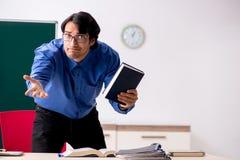 El profesor de sexo masculino joven delante de la pizarra imágenes de archivo libres de regalías