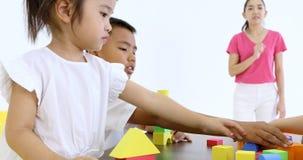 El profesor deja a los estudiantes que juegan bloques de madera juega metrajes