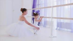 El profesor del ballet en el tutú blanco está entrenando a la niña cerca del soporte de la barra metrajes