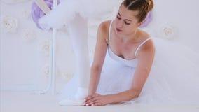 El profesor del ballet está ayudando a la niña a estirar los pies que levantan la situación de puntillas almacen de video