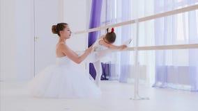 El profesor del ballet está enseñando a la niña a estirar las piernas cerca del soporte de la barra metrajes