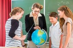 El profesor educa a los estudiantes que tienen lecciones de la geografía en escuela Fotografía de archivo libre de regalías