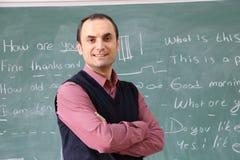 El profesor en la sala de clase en fondo del greenboard Imagen de archivo