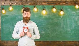 El profesor en lentes sostiene el despertador Horario y concepto del r?gimen El inconformista barbudo sostiene el reloj, pizarra  fotografía de archivo libre de regalías