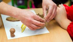 El profesor enseña al estudiante a esculpir con la arcilla Imagen de archivo