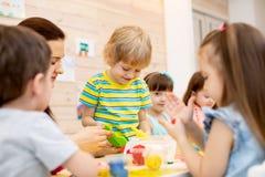 El profesor enseña a la arcilla de modelado de los niños en sala de juegos en la guardería fotos de archivo libres de regalías