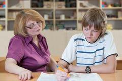 El profesor enseña a un alumno en una tabla en la sala de clase Fotografía de archivo