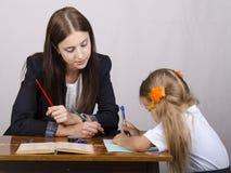 El profesor enseña a lecciones con un estudiante que se sienta en la tabla Foto de archivo