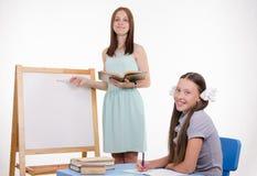 El profesor explica el tema de la lección en la pizarra Imagen de archivo libre de regalías