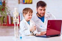 El profesor explica una estructura corporal humana al pequeño alumno con la ayuda del ordenador portátil Fotografía de archivo