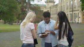 El profesor mayor de la geografía que habla con los estudiantes acerca a la universidad, explicando tema almacen de video