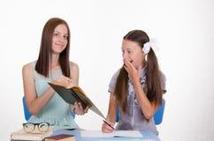 El profesor muestra el texto de estudiante en un libro de texto Imagen de archivo
