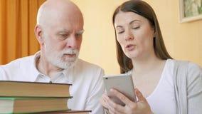 El profesor particular de sexo femenino explica al estudiante mayor cómo utilizar el uso en línea para aprender idiomas extranjer almacen de metraje de vídeo