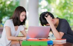 El profesor particular del estudiante enseña a su amigo antes de examinatuin en hacia fuera li de la puerta foto de archivo