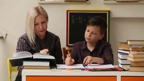 El profesor particular enseña a un colegial antes de exámenes helping