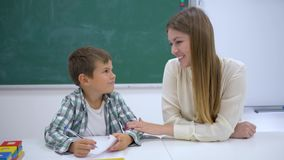 El profesor particular experimentado ayuda a aprender al colegial en la tabla cerca de tablero en la sala de clase de la escuela almacen de metraje de vídeo