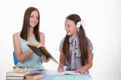El profesor particular muestra trabajo de la muchacha en el libro de texto Foto de archivo