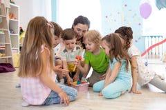 El profesor preescolar juega con el grupo de ni?os que se sientan en un piso en la guarder?a imagen de archivo libre de regalías