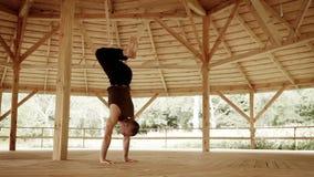 El profesor profesional de la yoga muestra posición del pino lisa en cente trauning de la alta montaña