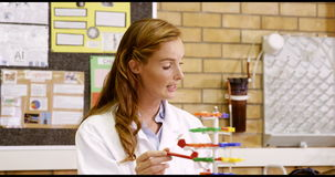 El profesor que ayuda a la escuela embroma con el modelo de la molécula en laboratorio almacen de video
