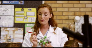 El profesor que ayuda a la escuela embroma con el modelo de la molécula en laboratorio metrajes