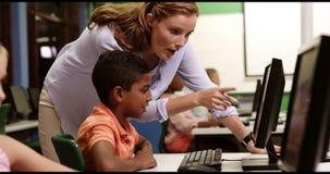El profesor que ayuda a la escuela embroma en de computadora personal en sala de clase