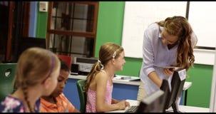 El profesor que ayuda a la escuela embroma en de computadora personal en sala de clase almacen de video