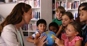 El profesor que ayuda a la escuela embroma en globo de la lectura en biblioteca almacen de video