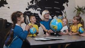 El profesor que ayuda a la escuela embroma en globo de la lectura en sala de clase de la geografía en la escuela primaria Un prof almacen de video