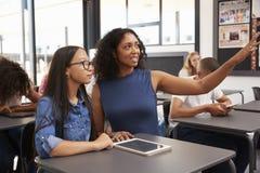 El profesor que trabaja con la colegiala adolescente señala al tablero fotografía de archivo