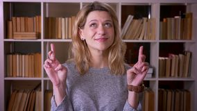 El profesor rubio de mediana edad lindo ruega con los fingeres cruzados para mostrar esperanza en c?mara en la biblioteca almacen de metraje de vídeo