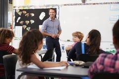 El profesor sonriente en el frente de la escuela primaria clasifica Fotografía de archivo