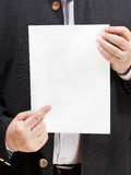 El profesor sostiene la hoja de papel en blanco en manos Imagen de archivo