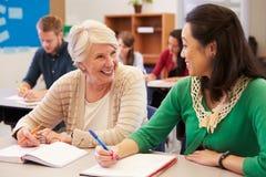El profesor y el estudiante se sientan juntos en una clase de la enseñanza para adultos Fotografía de archivo libre de regalías