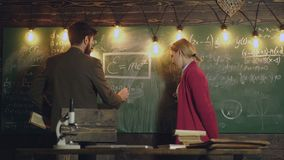El profesor y la estudiante barbudos deciden las fórmulas que se escriben en la pizarra Profesor y estudiante al lado de metrajes