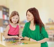 El profesor y la muchacha en la tabla que estudian las tarjetas Fotos de archivo libres de regalías