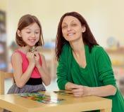 El profesor y la muchacha en la tabla que estudian las tarjetas Foto de archivo libre de regalías