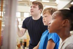 El profesor y los niños que miran una ciencia exhiben, se cierran para arriba fotografía de archivo