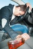 El programa piloto bebido joven duerme en el coche con la botella. Fotografía de archivo libre de regalías