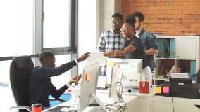 El programador africano joven que trabaja en oficina personal del estilo del computerloft es lleno de voluntarios ambiciosos jove almacen de metraje de vídeo