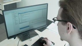 El programador en vidrios trabaja en el ordenador en la oficina metrajes