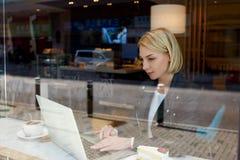 El programador remoto de sexo femenino elegante está utilizando el red-libro para el trabajo de la distancia imagen de archivo