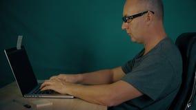 El programador se sienta en la tabla y la codificación en el ordenador portátil Manos del finger del hombre que mecanografían ráp metrajes