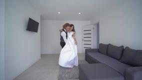 El prometido feliz lleva a la novia en las manos en el vestido blanco y gira en el nuevo apartamento el día de boda metrajes