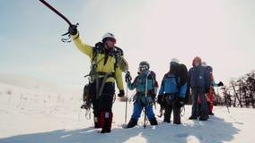 El promotor de carga señala el hacha de hielo en dirección de su manera el equipo se coloca en la nieve y estaba cansado metrajes
