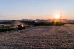 El propósito aéreo de la cosecha de la máquina segadora avena cosecha en la puesta del sol Fotos de archivo libres de regalías
