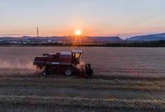 El propósito aéreo de la cosecha de la máquina segadora avena cosecha en la puesta del sol Fotos de archivo