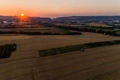 El propósito aéreo de la cosecha de la máquina segadora avena cosecha en la puesta del sol Fotografía de archivo