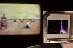 El proyector de diapositivas de la foto del vintage que muestra las fotografías viejas resbala en sitio oscuro Foto de archivo