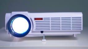 El proyector video moderno proyecta un vídeo en la pantalla Tiro del carro almacen de video